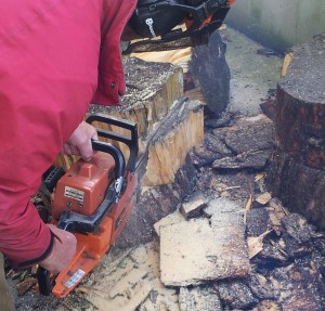 Using a chain saw to cut wood